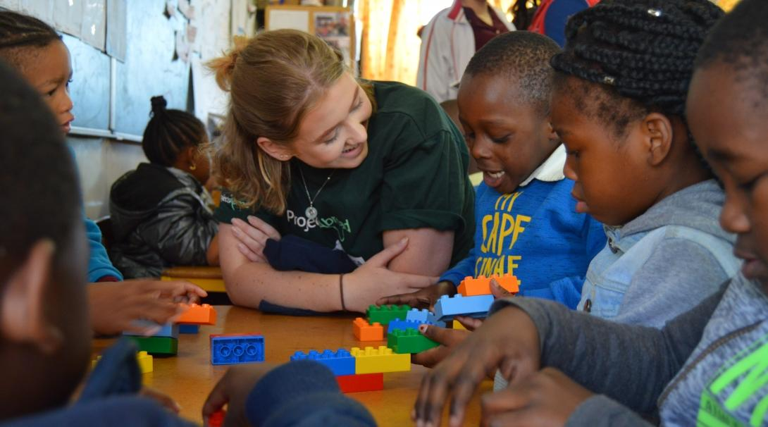 A volunteer and a group of South African children play a game on a Childcare Project in Africa